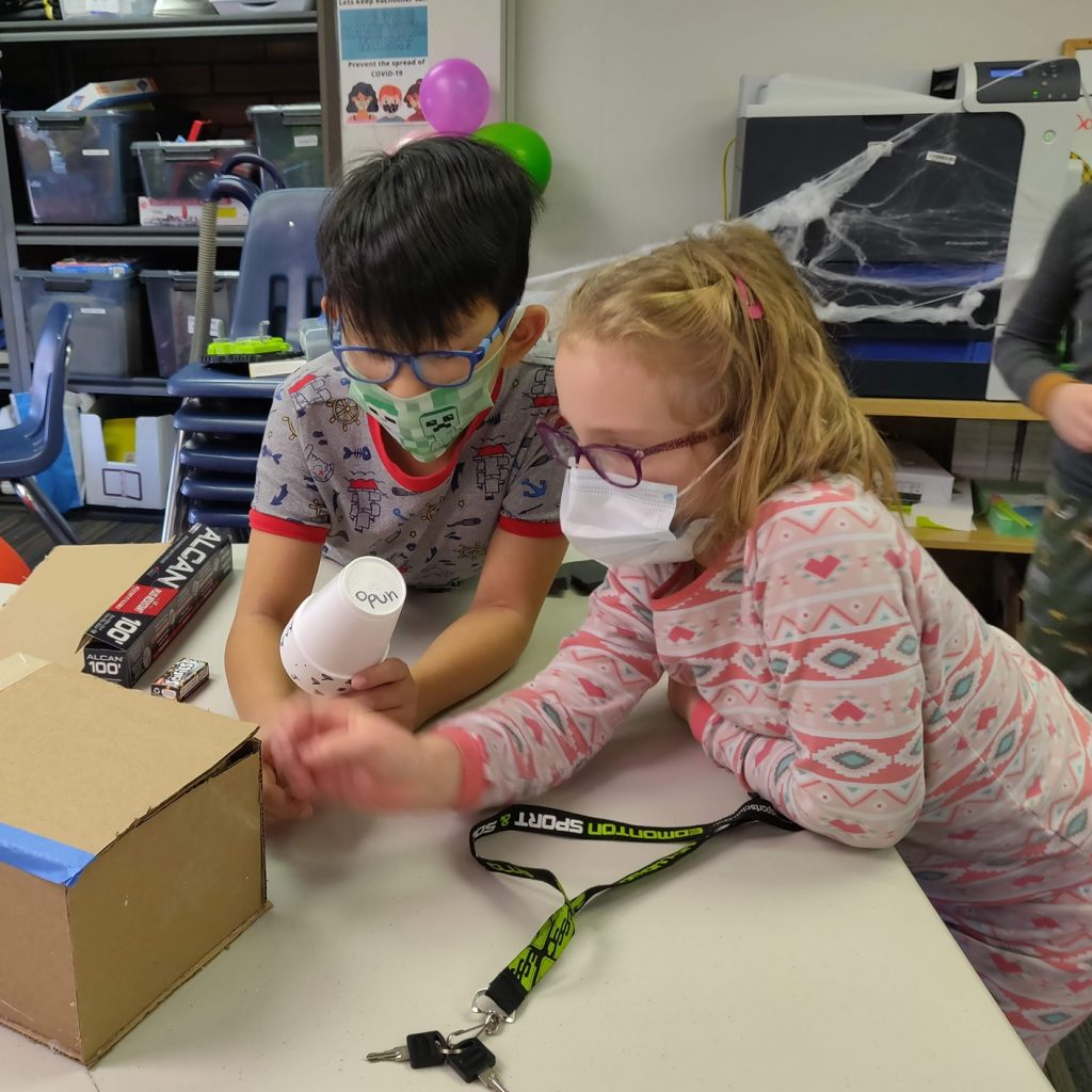 Children in Masks create crafts with cardboard box at Discover Coding.