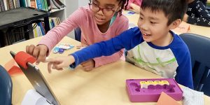 Image of two children learning Scratch coding and pointing at an iPad together.
