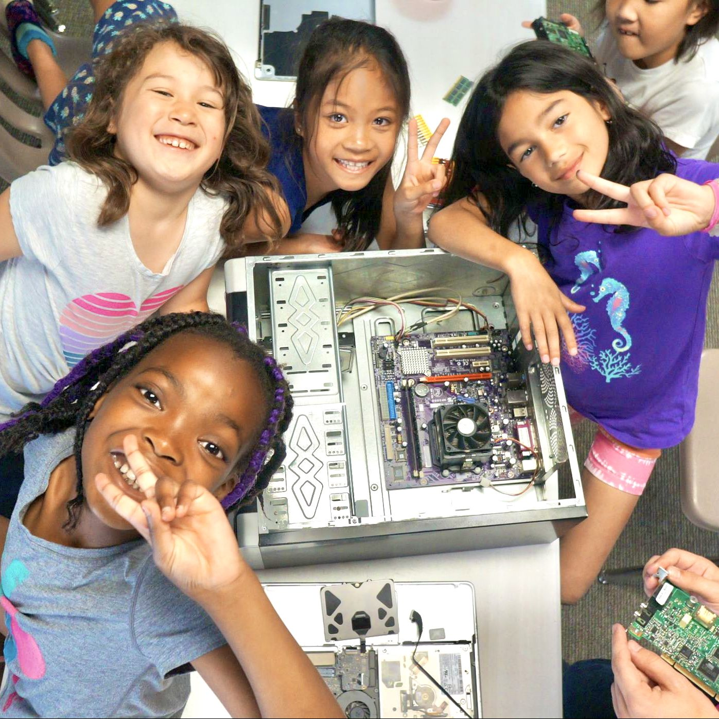 Group of four girls smile at the camera while building a computer at coding camp